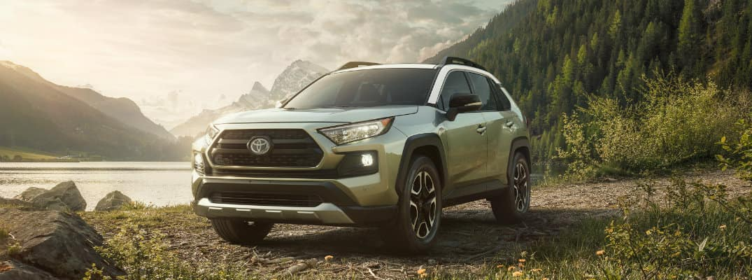 Image of a 2019 Toyota RAV4 parked by a lake in the mountains.
