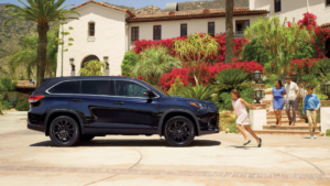 Image of a 2019 Toyota Highlander parked in a driveway with a family running toward it.