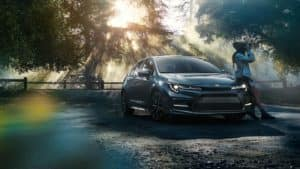 Image of a young woman leaning against a 2020 Toyota Corolla in the woods.