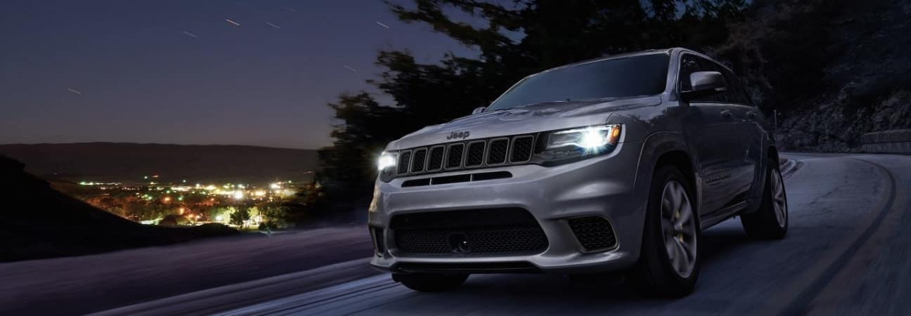 Silver 2018 Jeep Grand Cherokee driving through a starry night