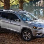 2019 Jeep Cherokee parked in the woods next to a lake