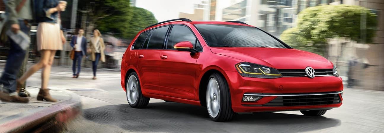 Red 2019 Volkswagen Golf SportWagen rounding street corner