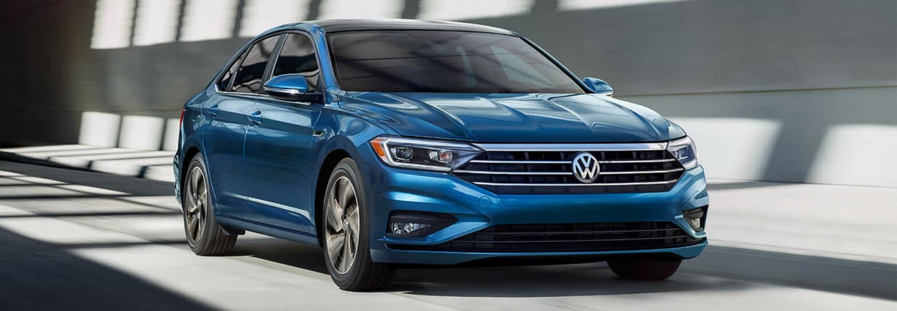 Blue 2019 VW Jetta driving on road
