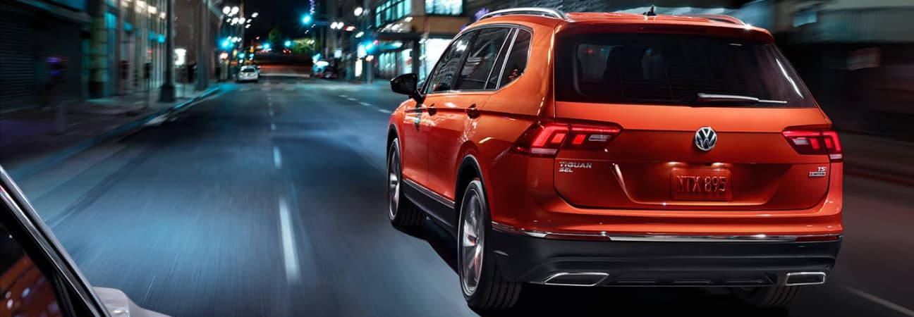 Orange 2018 Volkswagen Tiguan navigating through city streets