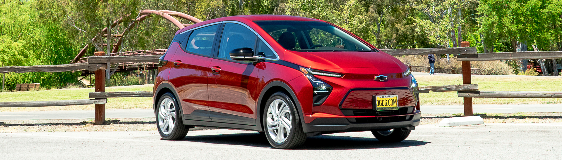 2022 Chevy Bolt EV 1LT in the color Cherry Red Tintcoat parked in a lot with a small bridge in the background.