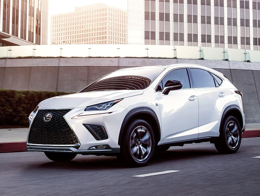 Image of a white Lexus NX SUV driving on a city street.